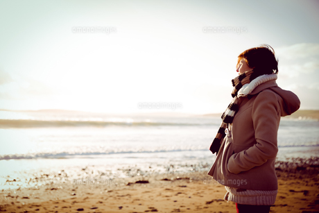 Slim woman looking at the sea during the sunsetの写真素材 [FYI00006690]