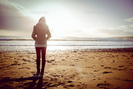 Rear view of woman looking at the sea during the sunsetの写真素材 [FYI00006696]