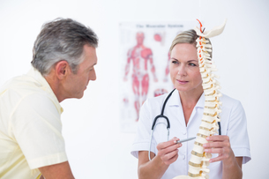 Doctor showing her patient a spine modelの写真素材 [FYI00006710]