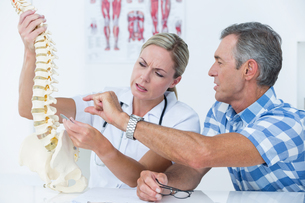 Doctor showing her patient a spine modelの写真素材 [FYI00006714]