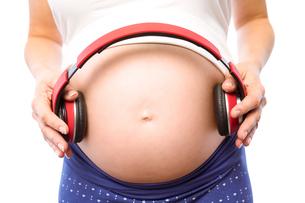Pregnant woman holding earphones over bumpの写真素材 [FYI00006715]