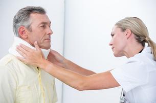 Doctor examining patient wearing neck braceの写真素材 [FYI00006720]