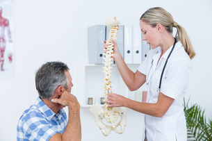 Doctor showing her patient a spine modelの写真素材 [FYI00006722]