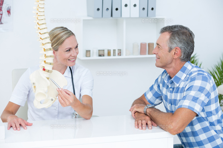 Doctor showing her patient a spine modelの写真素材 [FYI00006726]