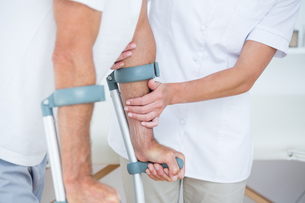 Doctor helping her patient walking with crutchの写真素材 [FYI00006727]