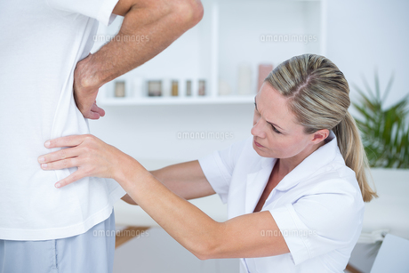 Doctor examining her patient backの写真素材 [FYI00006733]