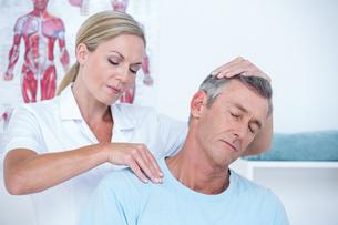 Doctor examining her patient neckの写真素材 [FYI00006749]