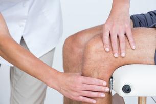 Doctor examining her patient kneeの写真素材 [FYI00006762]