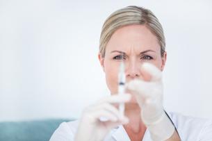 Doctor preparing syringeの写真素材 [FYI00006768]