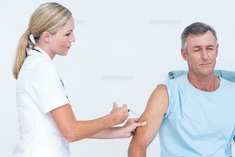 Doctor doing an injection to her patientの写真素材 [FYI00006769]