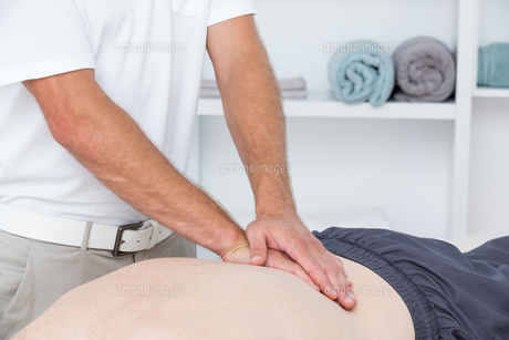 Physiotherapist doing back massage to his patientの写真素材 [FYI00006786]
