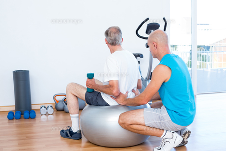 old man having back massage on exercise ballの写真素材 [FYI00006796]