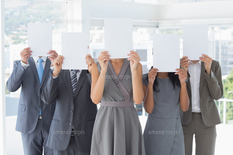 Business colleagues hiding their face with paperの写真素材 [FYI00006800]