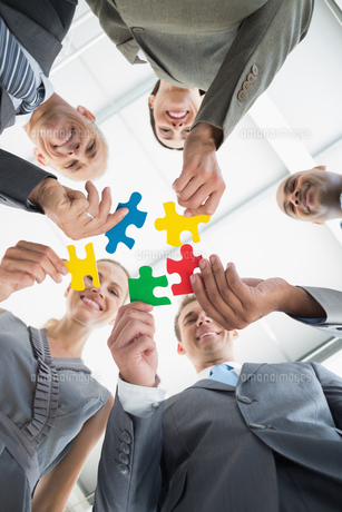 Business colleagues holding piece of puzzleの写真素材 [FYI00006806]