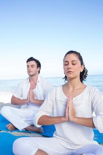 Happy couple doing yoga beside the waterの写真素材 [FYI00006832]