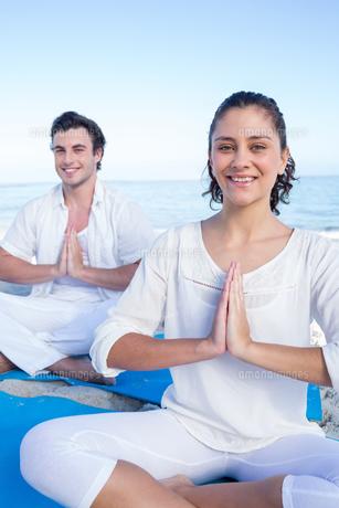 Happy couple doing yoga beside the waterの素材 [FYI00006833]