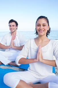Happy couple doing yoga beside the waterの写真素材 [FYI00006833]