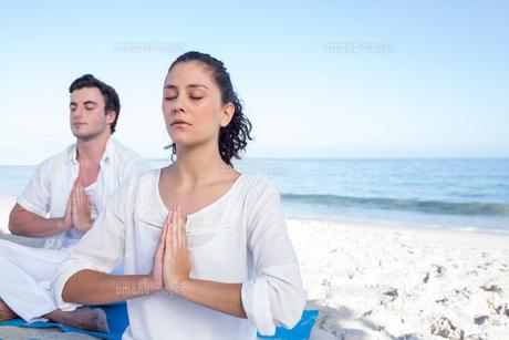 Happy couple doing yoga beside the waterの写真素材 [FYI00006834]