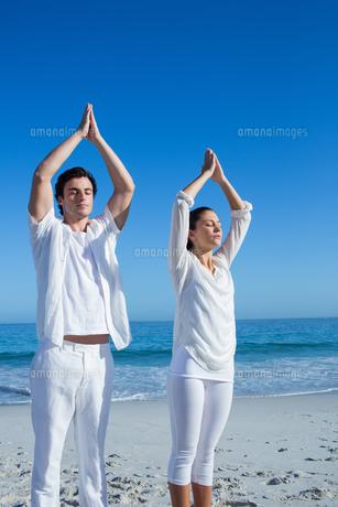 Happy couple doing yoga beside the waterの写真素材 [FYI00006839]