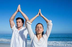 Happy couple doing yoga beside the waterの写真素材 [FYI00006841]