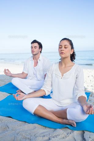 Happy couple doing yoga beside the waterの素材 [FYI00006844]