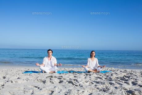 Happy couple doing yoga beside the waterの素材 [FYI00006845]