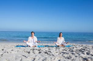 Happy couple doing yoga beside the waterの写真素材 [FYI00006845]