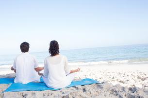 Happy couple doing yoga beside the waterの写真素材 [FYI00006849]