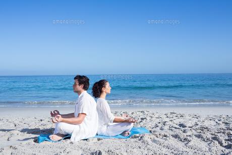 Happy couple doing yoga beside the waterの素材 [FYI00006856]