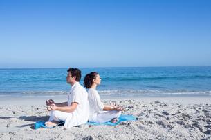 Happy couple doing yoga beside the waterの写真素材 [FYI00006856]