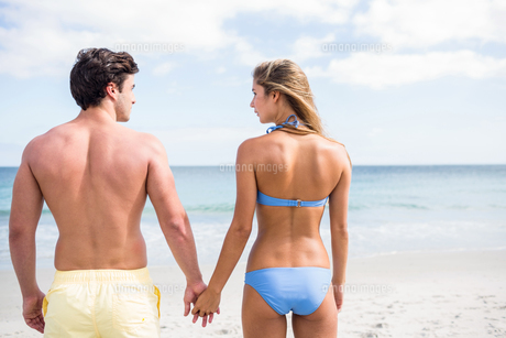 Happy couple holding hands and looking at the seaの写真素材 [FYI00006876]