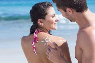 Handsome man putting sun tan lotion on his girlfriendの写真素材 [FYI00006901]