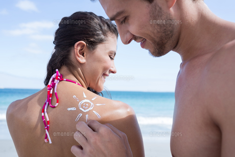 Handsome man putting sun tan lotion on his girlfriendの写真素材 [FYI00006904]