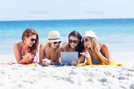 Happy friends wearing sun glasses and using tabletの写真素材 [FYI00006934]