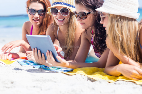 Happy friends wearing sun glasses and using tabletの写真素材 [FYI00006937]