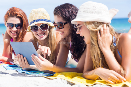 Happy friends wearing sun glasses and using tabletの写真素材 [FYI00006944]