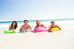 Happy friends lying on inflatable mattress above the waterの写真素材 [FYI00006959]
