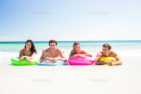 Happy friends lying on inflatable mattress above the waterの写真素材 [FYI00006960]