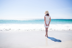 Pretty brunette wearing straw hat and walking in the waterの写真素材 [FYI00006974]