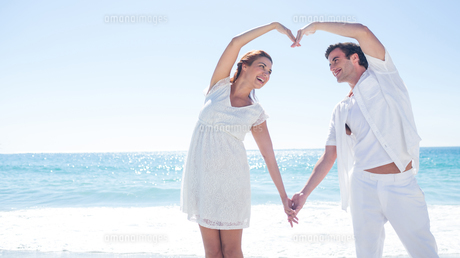 Happy couple forming heart shape with their handsの素材 [FYI00006975]