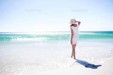 Pretty brunette wearing straw hat and walking in the waterの写真素材 [FYI00006976]