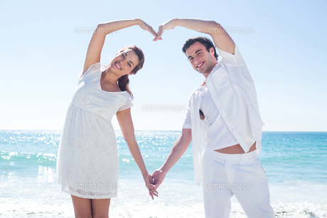 Happy couple forming heart shape with their handsの素材 [FYI00006980]