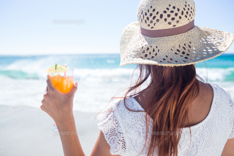 Brunette wearing straw hat and holding a cocktailの素材 [FYI00006983]