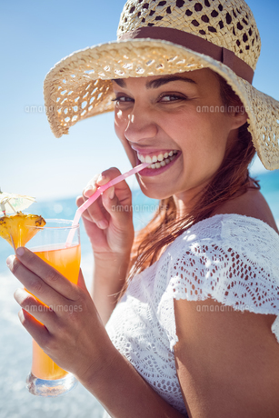 Smiling brunette wearing straw hat and drinking a cocktailの素材 [FYI00006989]