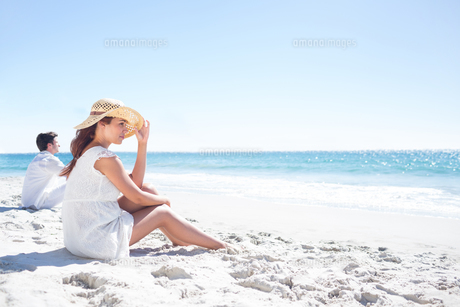 Brunette sitting in the sand and looking at the seaの素材 [FYI00006990]