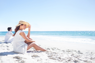 Brunette sitting in the sand and looking at the seaの写真素材 [FYI00006990]