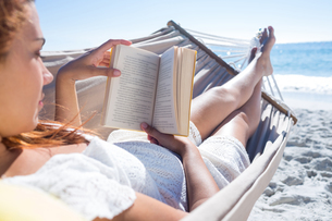 Brunette reading a book while relaxing in the hammockの写真素材 [FYI00007018]