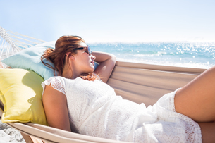 Brunette relaxing in the hammock with sunglassesの写真素材 [FYI00007019]