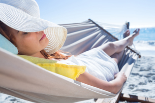 Brunette relaxing in the hammockの写真素材 [FYI00007020]