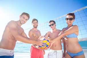 Group of friends holding volleyball and smiling at cameraの素材 [FYI00007036]